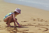 child playing in the sand at Maui Ulua Beach